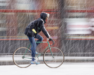 Man on bicycle in the city in snowy winter day