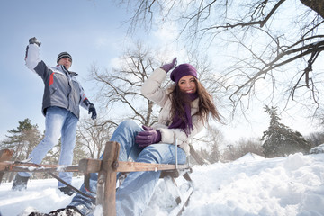 joyful man throwing snowball at woman