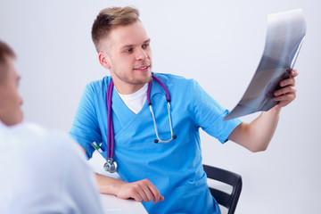 Male doctor explaining spine x-ray to patient in the medical