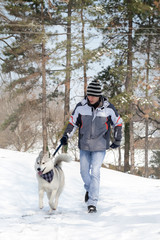 Man walking his dog in snowy forest