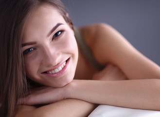 Closeup of a smiling young woman lying on couch at home