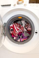 Closeup of an open washing machine full of dirty laundry to wash