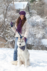 Girl with dog in snowy forest