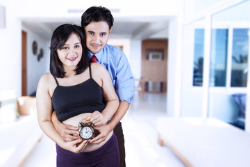 Young parents with alarm clock
