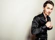 Elegant young handsome man in black silk shirt.
