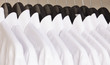 row of cloth hangers with white shirts