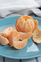 Peeled tangerine on a blue plate with white background.
