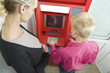 Woman trains the child to receive money from the bank atm device