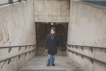 Young handsome bearded man posing on stairs