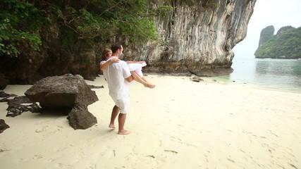 groom carries bride in arms at beach of sea
