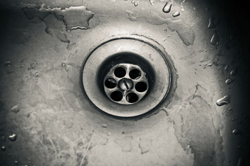 Drain hole in a dirty sink close up