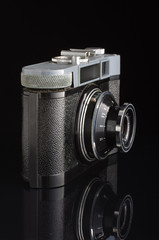 Obsolete film camera isolated with reflection