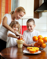 Mother with children squeezed orange juice