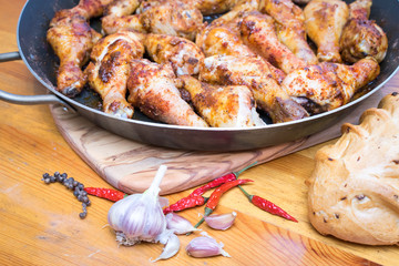 Roasted chicken drumsticks on a frying pan
