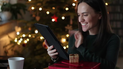 Woman chatting on tablet computer. Christmas tree in background