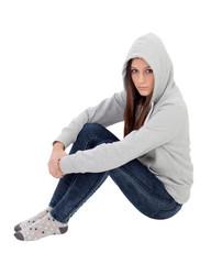 Angry hooded girl with grey sweatshirt sitting on the floor