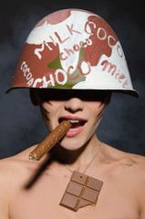 Beautiful woman with chocolate cigar and helmet