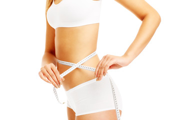 Midsection of a fit woman measuring her waist