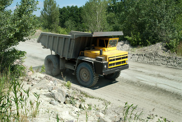 Yellow dump truck driving on a road in a stone quarry