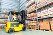 Asian fork lift truck driver lifting pallet in storage - 77316249