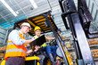 Leinwanddruck Bild - Asian forklift truck driver and foreman in storage