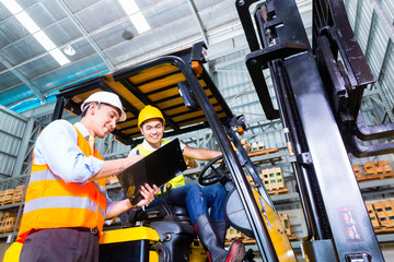 Asian forklift truck driver and foreman in storage