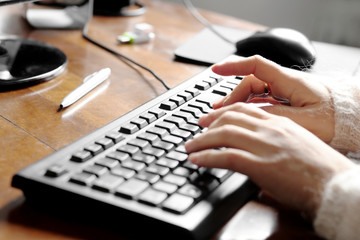 female hands over office desk typing over keyboard