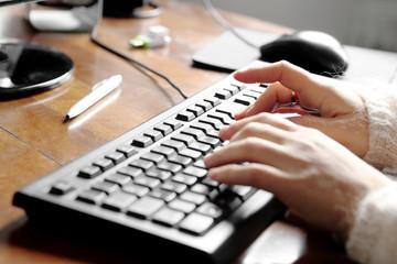female hands over office desk typing over keyboard