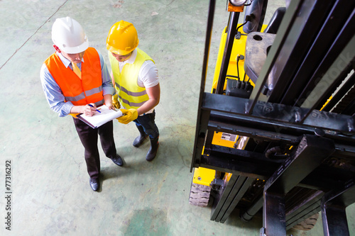 forklift truck driver and foreman in storage - 77316292