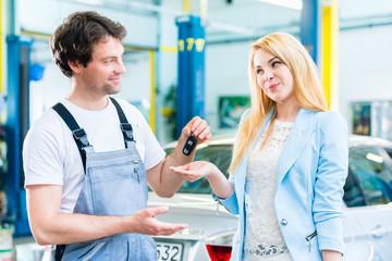 Autowerkstatt Mechaniker übergibt Auto an Kundin