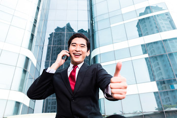 Asian business man talking outside to mobile phone