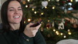 Happy young woman watching tv in front of christmas tree