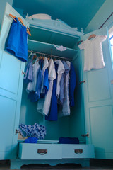 Dressing closet with blue clothes in the closet