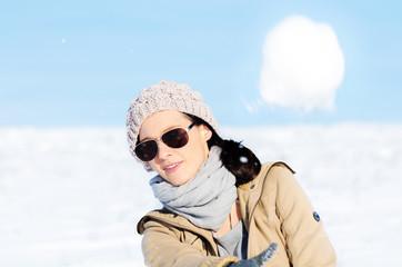 Frau wirft einen Schneeball