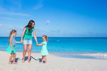 Young happy mother and little girl having fun during beach