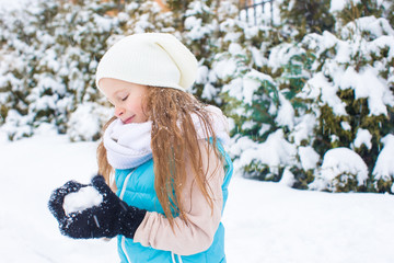 Happy adorable girl playing snowballs in snowy winter day