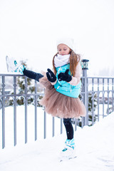 Adorable little girl skating in winter snow day