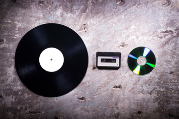 vinyl, cassette tape and CD on a concrete background