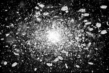 Freeze motion of white powder glass exploding black background