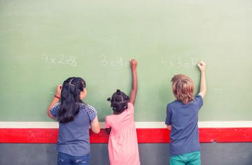 Multi ethnic schoolmates writing math at chalkboard