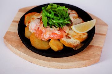 Salmon baked with potatoes and lemon on a cast iron skillet