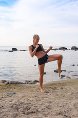 Attractive Young Woman Doing Exercise on the Beach