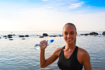 Young female in sports attire rests with water