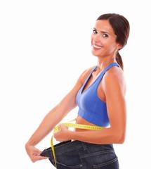 Smiling woman in sportswear pulling jeans on waist