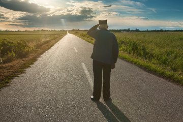 Old farmer standing in middle of the road
