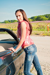 Beautiful brunette female standing near car