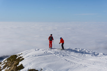 Two skiers on top of mountain above the clouds