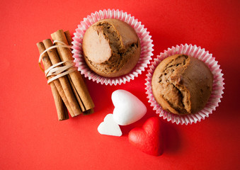 muffin and cinnamon with hearts on red background