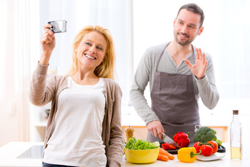 Young attractive woman taking selfie in kitchen