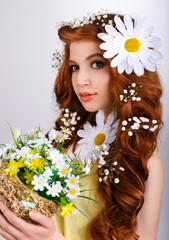 red-haired girl with daisies in her hair holding a bouquet